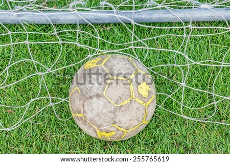 Old football on grass with net - stock photo