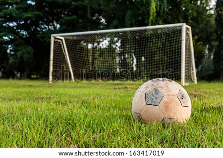 Old football on lawn in rural school - stock photo