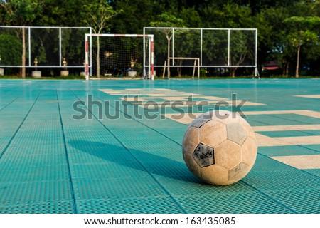 Old football on yard in rural school holiday - stock photo