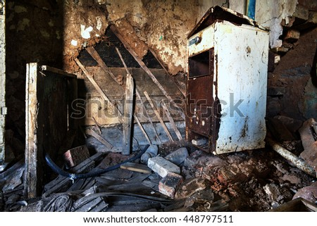 Old forgotten and abandoned home interior in a derelict decaying state with grimy floors and ripped wallpaper and a disused fridge. - stock photo