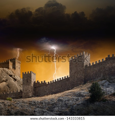 Old fortress on rock struck by lightning from dark red sky - stock photo