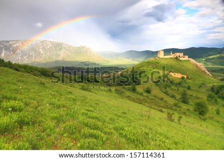 Old fortress under overcast sky and rainbow