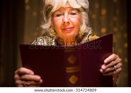 Old fortune teller is reading a dream book - stock photo