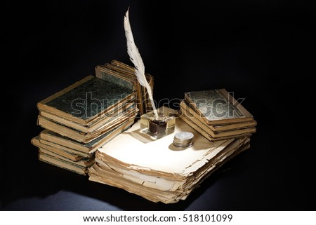 Old fountain pen, papers and inkwell and silver coins on a black background