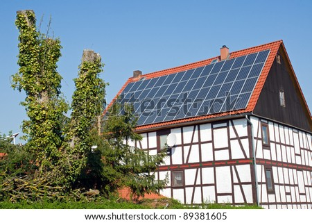 Old frame house with solar cells on the roof - stock photo