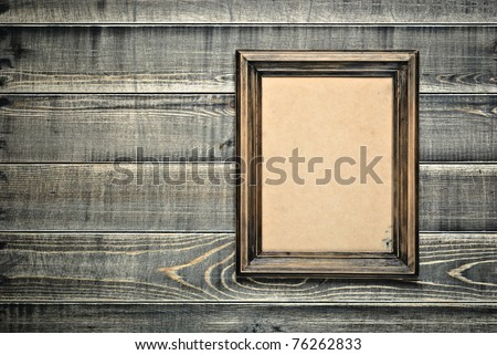 Old frame with an empty cardboard a on wooden wall - stock photo