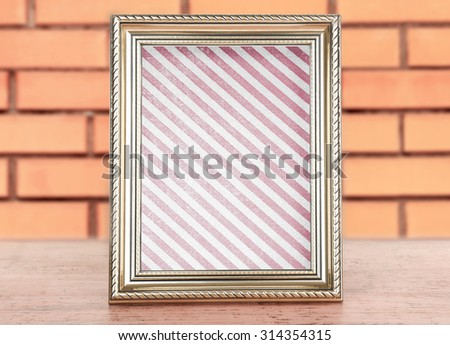 Old frame with striped canvas standing on table on brick wall background - stock photo