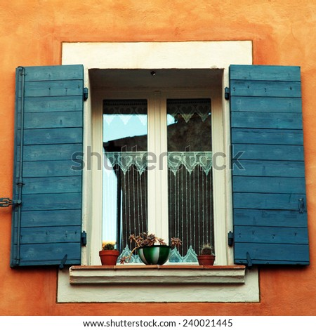 old french open window with blue shutters in red rural house, Provence, France. square toned image, instagram effect - stock photo