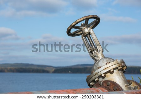 Old fuel pipe valve in an abandoned harbor - stock photo