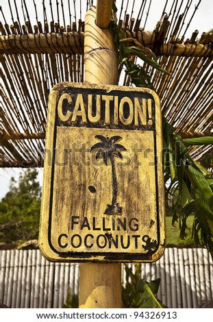 Old funny wooden caution sign on the beach. - stock photo