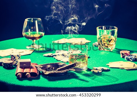 Old gambling table with whiskey, cigar and cards - stock photo