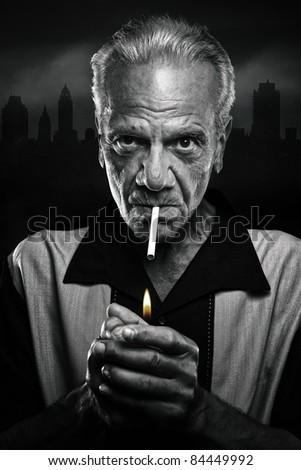 Old Gangster Lighting a Cigarette - stock photo