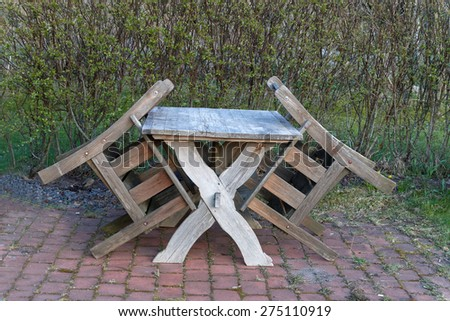 Old garden furniture, one table and two chairs in upright position standing on cobblestone in front of a hedge - stock photo
