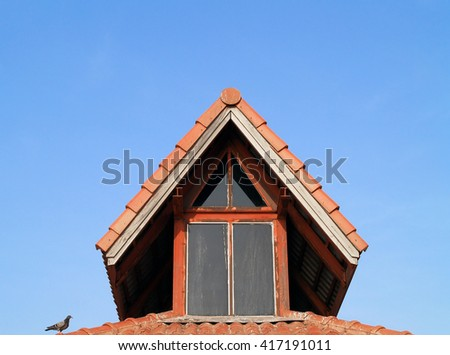 old garret with bird perched on red brick roof tiles and blue sky - stock photo
