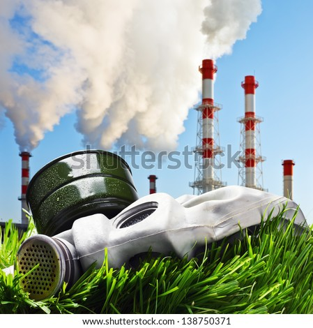 old gas mask on a green grass on a background of smoking chimneys polluting the planet - stock photo