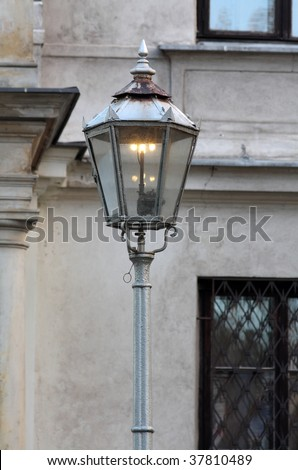 Old gas powered lamp post against wall. - stock photo
