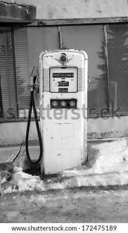 Old gas pump at an abandoned gas station in black and white - stock photo