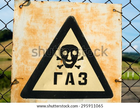 Old Gas sign (Cyrillic inscription) on the metal mesh. Close up. - stock photo
