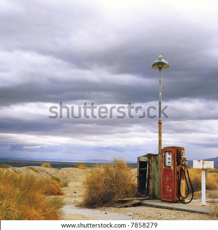 Old gas station in ghost town along the route 66 at border of the desert - stock photo