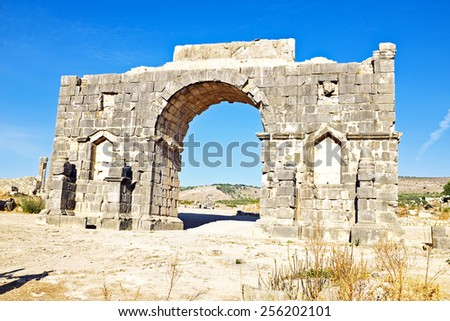 Old gate at Volubilis in Morocco. Volubilis is a partly excavated Roman city in Morocco situated near Meknes between Fes and Rabat. - stock photo