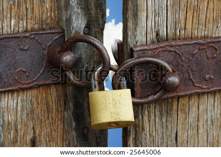 Old gate locked with blue sky in background. - stock photo