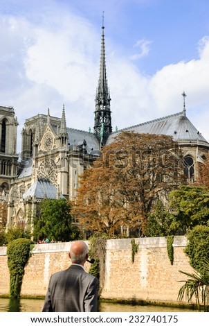 Old gentleman with pipe looking on Notre Dame cathedral (Paris, France.) Thinking about time, life, god... - stock photo