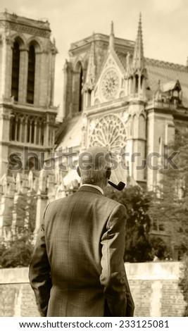 Old gentleman with pipe looking on Notre Dame cathedral (Paris, France.) Thinking about time, life, god...  Aged photo. Sepia. - stock photo