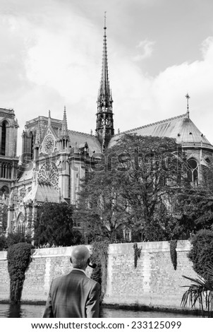Old gentleman with pipe looking on Notre Dame cathedral (Paris, France.) Thinking about time, life, god...  Aged photo. Black and white. - stock photo