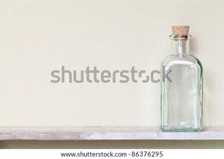 Old glass bottle on a shelf - stock photo