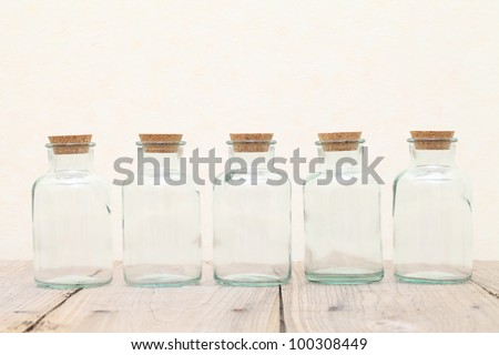 Old glass bottle on wooden table - stock photo