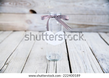 Old glass bottle with heart on wooden background. concept - stock photo