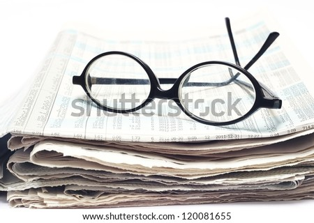 old glasses on newspaper - stock photo