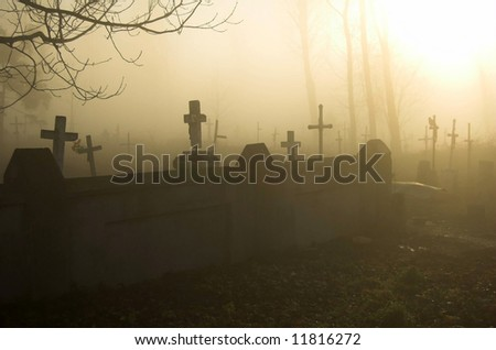 Old gloomy cemetery in a morning fog - stock photo