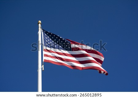 Old Glory American Flag Waving and Flying in the Blue Sky Background