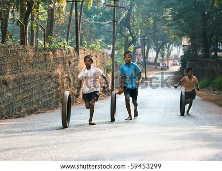 OLD GOA , INDIA -FEBRUARY 27: Children running and playing with old tyre in the Old Goa street, February  27, 2009. Old Goa, India - stock photo