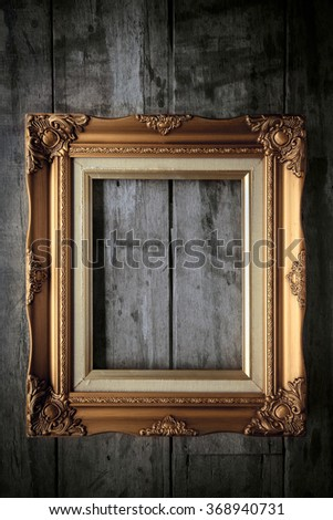 old gold frame on wood wall - stock photo