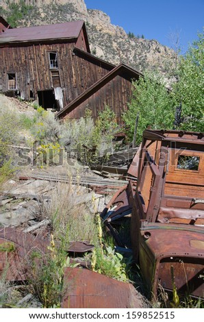 Old gold mining structure and rusted antique car at Bayhorse, Idaho ghost town. - stock photo