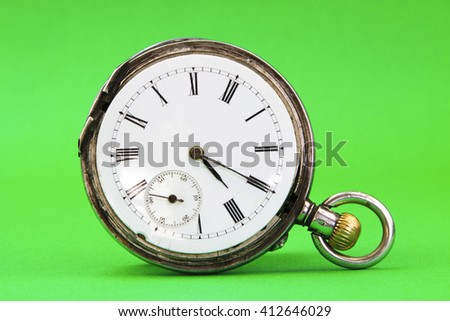 Old gold pocket watch isolated on green background - stock photo