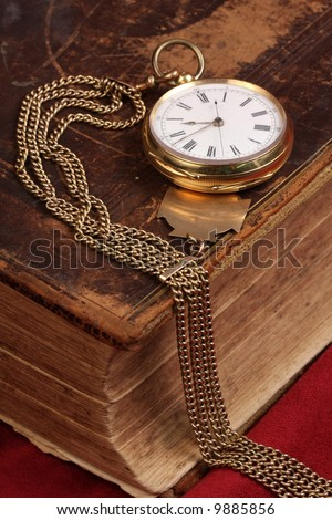 old gold pocket watch on antique bible book