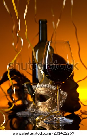 Old gold Venetian masks and red wine - stock photo