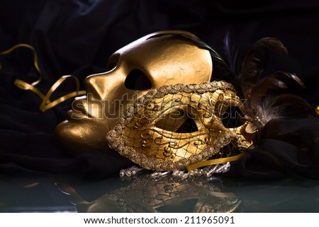 Old gold Venetian masks on a glass table