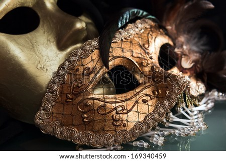 Old gold Venetian masks on  glass table