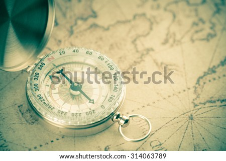 Old  gold vintage compass on vintage map:Heading south ;vintage tone style - stock photo