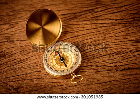 Old  gold vintage compass on wood background - stock photo