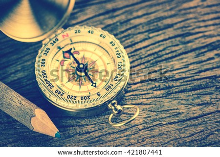 Old  gold vintage compass with pencil on wood background;vintage tone style - stock photo