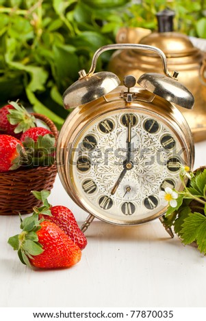 Old golden alarm-clock, old teapot and fresh strawberries on white table - stock photo