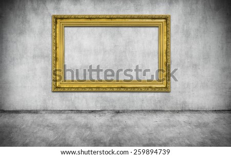 old golden empty frame on gray wall - stock photo