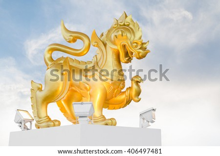 old golden lion statue and blue sky with clouds