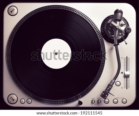 Old good looking turntable playing a track from black vinyl. Top view, vintage cross processing. - stock photo