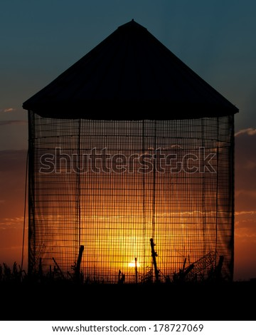 Old Grain Bin Sunset Silhouette - stock photo